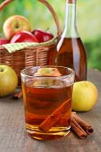 Apple cider in glass and bottle, with cinnamon sticks and fresh apples on wooden table, on bright background