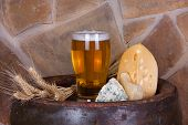 Glass of beer cheese and ears on old barrel with iron rings