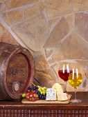 Wine, cheese, grapes and old wooden barrel with iron rings; still life