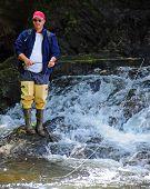 Fly Fisherman at Base of Waterfall