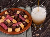 Glass of beer cheese and smoked sausages plate
