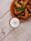 Beer and chicken wings on wooden background top shot