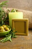 Bars of natural soap with rosemary and olive oil, candle and bowl with olives on wooden background