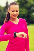 sport, fitness, technology, healthcare and people concept - smiling young woman with heart rate watch outdoors