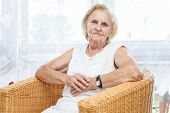 pic of 70-year-old  - Portrait of an elderly lady in her 70s sitting in a chair - JPG