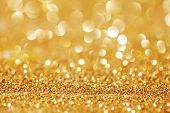 Golden Glitter for Christmas Background with Blurred Lights.