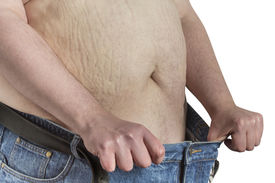 stock photo of bulging belly  - overweight shirtless Man stretching his blue jeans isolated on white background - JPG