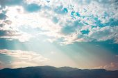 stock photo of cloud formation  - Ray of light sunset behind clouds with dramatic clouds and silhouette mountains Cross processing - JPG