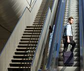 picture of escalator  - Portrait of a handsome man walking up escalator with travel bags - JPG