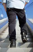 image of escalator  - Rear view low angle man standing on escalator - JPG