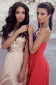 picture of beside  - fashion outdoor photo of two beautiful girls with dark hair in luxurious dresses posing beside old castle - JPG