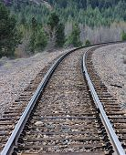 picture of railroad car  - A rail line winds its way through trees and forests in rural America - JPG
