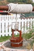stock photo of pulley  - Close up Water Well With Pulley and Bucket - JPG