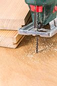 stock photo of fret  - Wood planks cutting with electric fret saw tool - JPG