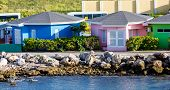 pic of curacao  - Blue pink and green stucco cabanas on the shore of Curacao - JPG