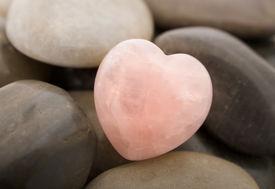 stock photo of valentine heart  - Rose quartz heart on pebbles - JPG