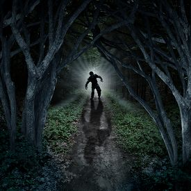 pic of scary haunted  - Horror monster walking in a dark forest as a scary fantasy concept with a creepy thing coming out of a remote wilderness background with a moon glow behind it as a halloween fear symbol of haunted woods and panic anxiety - JPG