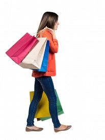 stock photo of heavy bag  - back view of going  woman  with shopping bags  - JPG