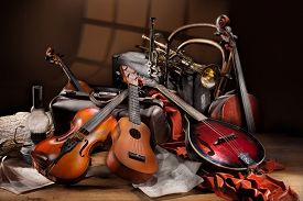 pic of string instrument  - Still life with different musical instruments notes and old suitcases on a wooden table - JPG