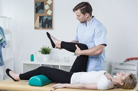 picture of knee  - Male physiotherapist exercising with patient having knee pain - JPG