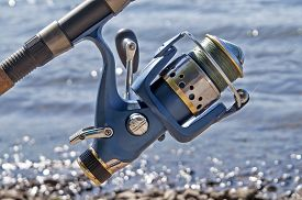 foto of coil  - The blue coil for fishing on a spinning in the sunny summer day - JPG