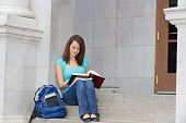 Young female student reading on campus