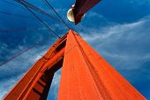 Bright Orange Golden Gate Bridge Tower And Lamp Post Rise Into Bright Blue Sky