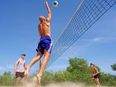Three Men Playing Beach Volleyball - Balding Man Strikes Ball With Fist