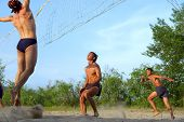 Three Men Playing Beach Volleyball - Two Teens Ready To Take The Ball (Focus On Closest Man)