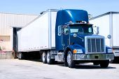 foto of semi  - This is a picture of 18 wheeler semi truck loading at a warehouse building - JPG