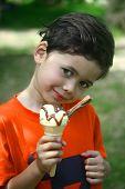 A young boy enjoying his ice cream cone in the garden.