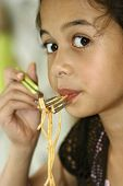A young girl enjoying her spaghetti with tomato sauce