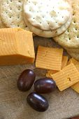 Cheese and biscuits served on wooden tray with red seedless grapes.