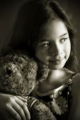 A young girl enjoying a quiet moment with her favourite cuddly toy. Rendered duotone suggestion of v