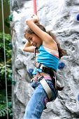 Young girl being lowered down by the safety rope from the indoor rock climbing activity.