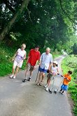 Family enjoying a walk in the countryside. Grandparents, parent, a daughter and a son.