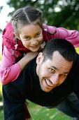 Junger Vater heben seine Tochter Sie auf dem Rücken, als sie zusammen im Park spielen