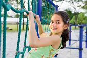 Young girl enjoying the climbing rope activity in the playground