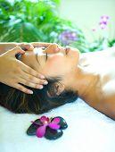 Joven disfrutando de un masaje holístico en spa tropical.