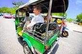 Senior with grandaughter enjoying a fast ride on Bangkok's most popular method of transportation,the