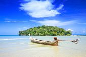 A lone tailboat waits by the shore for the tide to come in at Krabi bay, Thailand, with clear blue w