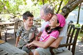Grandfather spending wonderful time with grandchildren. Concept of love, affection and appreciation.