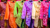 Beautiful '' Kebaya '' in all sorts of pretty colours hung up for sale . '' Kebaya '' is a traditional costume of the Malay Indonesian in Asia