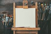 Artistic Equipment In A Artist Studio: Empty Artist Canvas On Wooden Easel And Paint Brushes Retro T poster