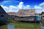 Wooden thatched roof houses on stilts in a water's village near Tuaran, Sabah Malaysia