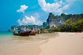 Famous long tail boats at Railay Bay overlooked by limestone cliffs off Krabi, Thailand