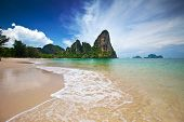 Famous limestone cliffs of Krabi bay overlooking wide sandy beach off west coast of Thailand