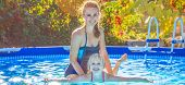 Happy Active Mother Teaching Daughter To Swim In Swimming Pool poster