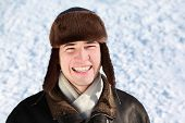 Youth in winter stands on snow in ear-flaps hat and laughs