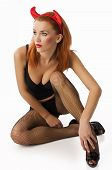 stock photo of fetish fishnet stockings  - sexy devil in black lingerie and stockings with red horns - JPG